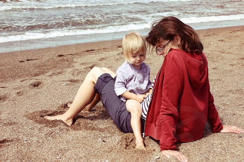 mother kid girl child toddler beach love family talking bonding woman summer sand photo
