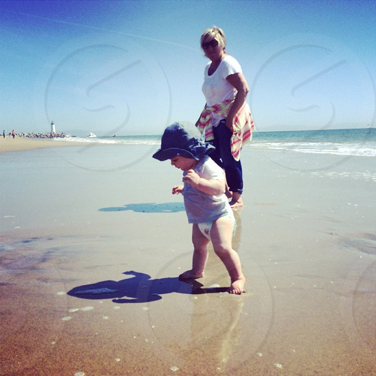 baby in blue hat walking on beach sand with woman in white t shirt black sunglasses  photo