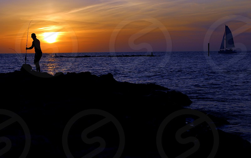 silhouette sunset ocean beach sea sailboat sky fishing photo