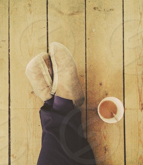 Legs crossed at ease next to a cup of tea/coffee photo