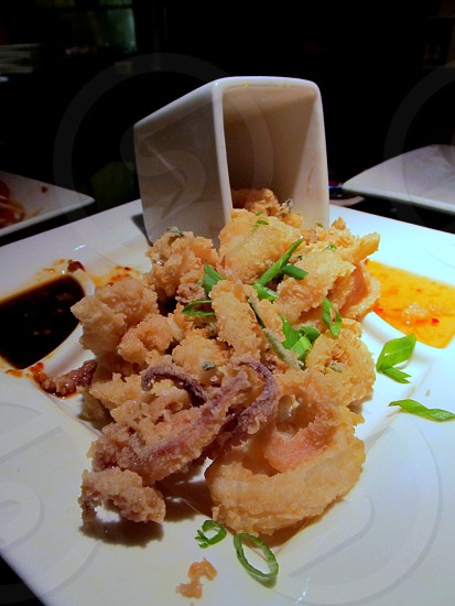Fried calamari spilling out of take-out container photo