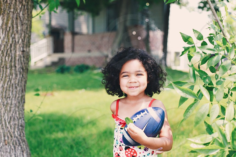 girl holding blue football under the tree photo
