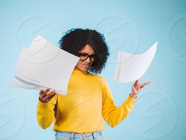 Angry young afro american businesswoman or student is scattering documents on blue background. photo