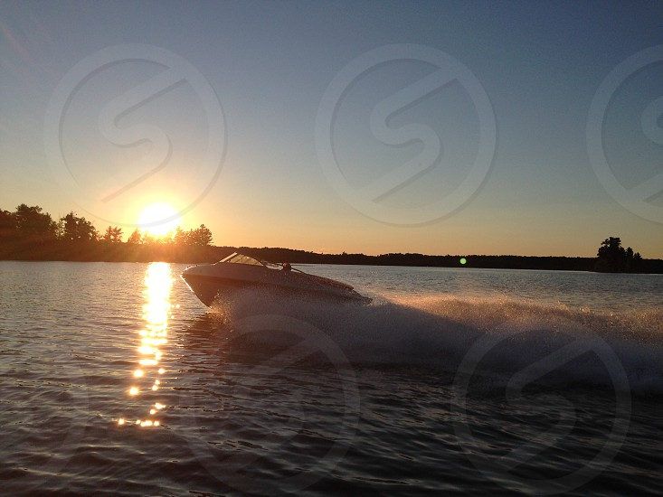 photo of person riding motorboat during daytime photo