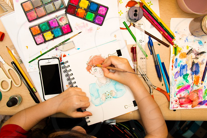 person painting a girl cartoon character on white sketchpad beside smartphone and surrounded with art material photo