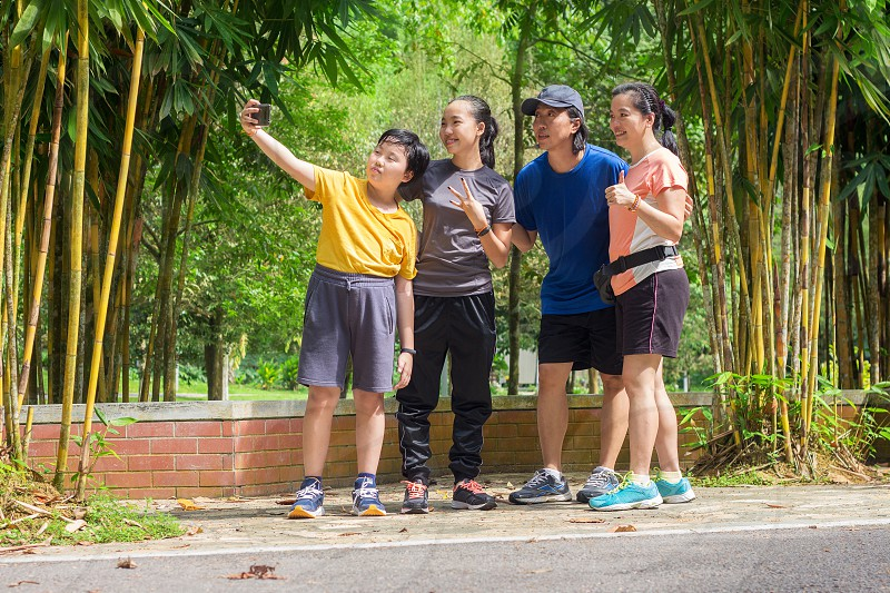 asian family happily taking selfie photo using smart phone in a park wearing sportswear photo