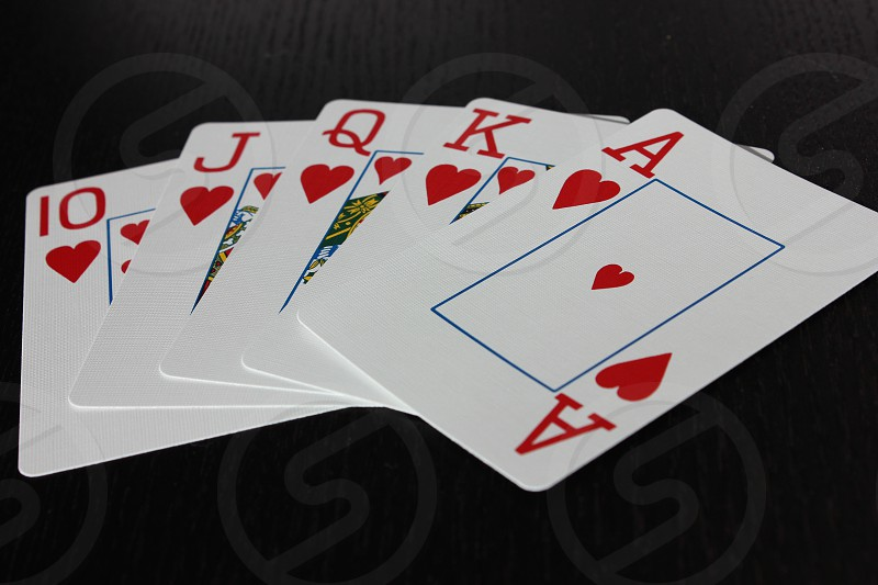 hearts royal flush cards fanned out on a table photo