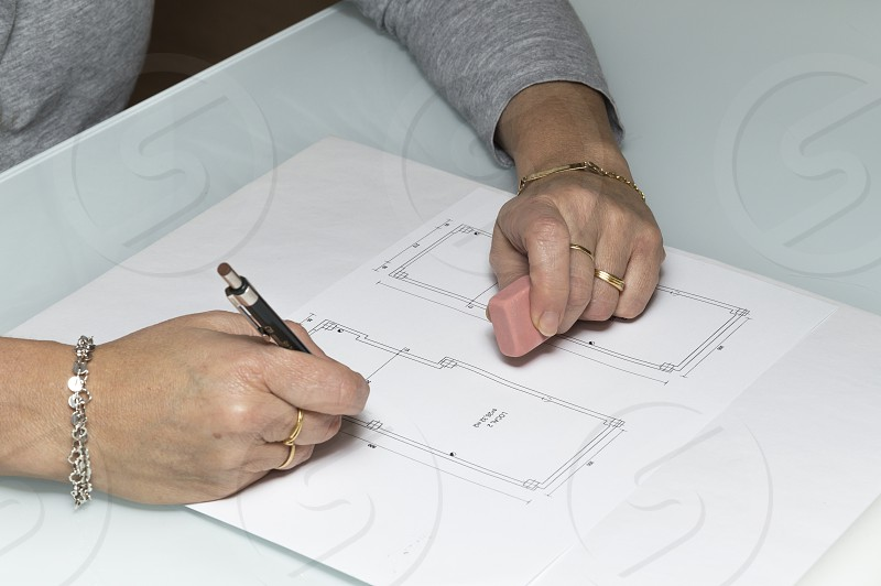 Architect woman making notes in a drawing with a pencil photo