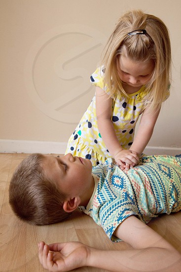 girl doing cpr to a boy photo