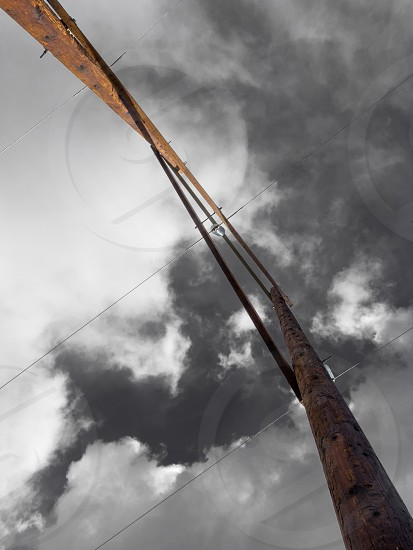 Wooden poles of high voltage electric power transmission line from right underneath against dramatic cloudy sky photo