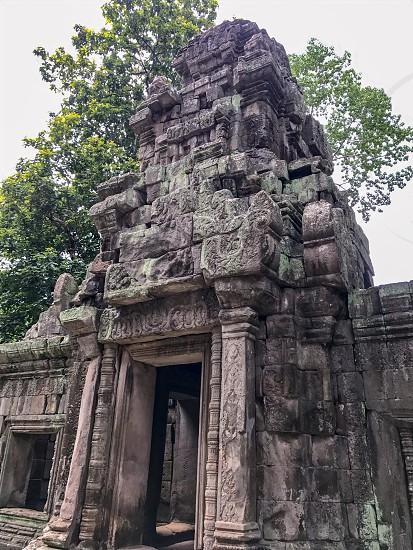 Outdoor day colour vertical portrait Angkor Angkor National Park Siem Reap Cambodia Asia Asian east eastern ancient holy spiritual Khmer dynasty monument sky blue white clouds summer travel tourism tourist wanderlust stone carved ornate elaborate figure figures temple grounds ruin ruined trees door doorway photo