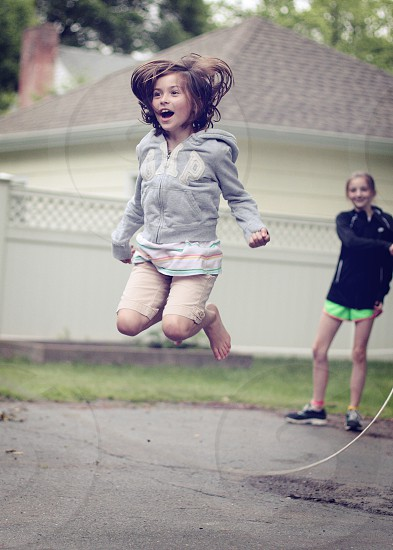 A young girl jumps rope outside as her sister looks on. photo