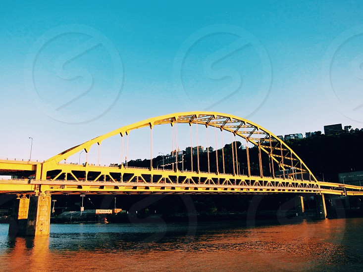 low angle photography of bridge with body of water with a silhouette buildings on back with teal  and white sky photo