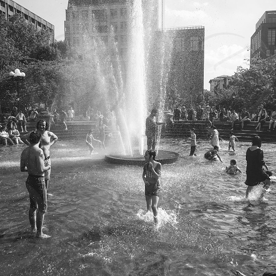 grayscale photography of people gathering near fountain photo
