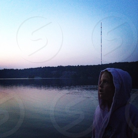 Evening by the lake. Young girl contemplating. photo