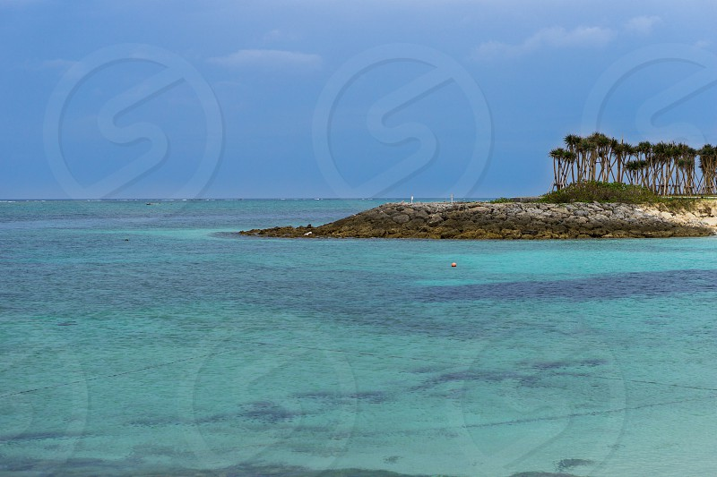 body of water and green and white island under blue sky photo