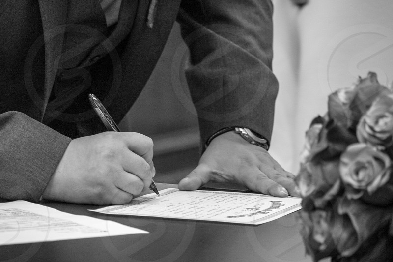 Groom signing his marriage certificate. photo