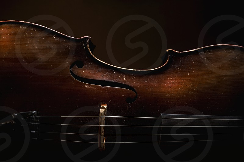 Part of an old dusty cello details of old wood and strings accentuated shapes in dark. photo