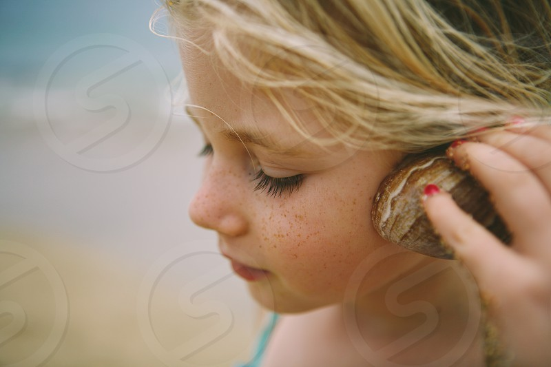 little girl listening to sea shell at beach photo