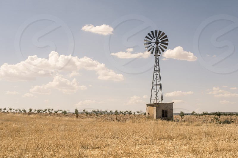Old windmill at blue cloudy sky photo