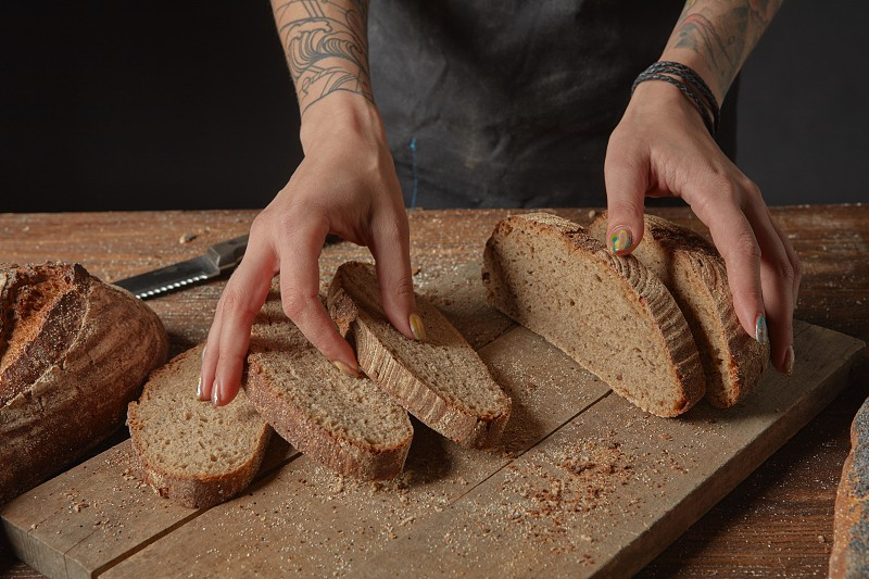 Man with cut bread in kitchen on a wooden background photo