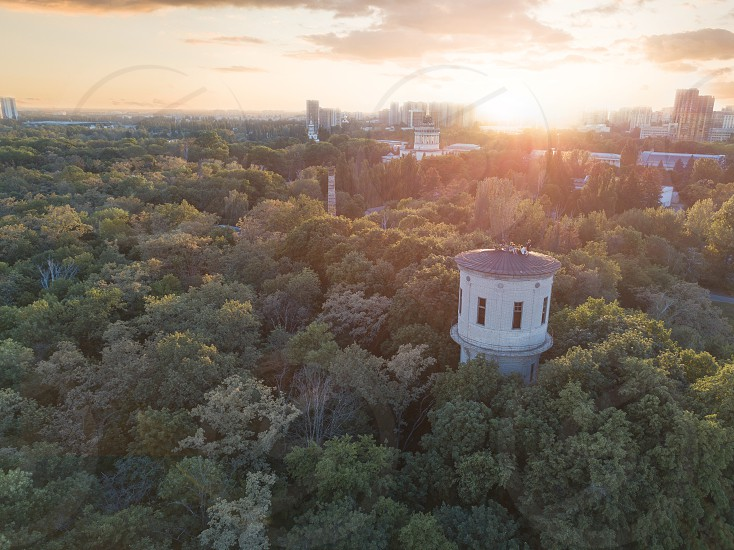 A city in the distance and a green park with a tower and people on the roof against the sky with the sunset. Aerial view from the drone photo