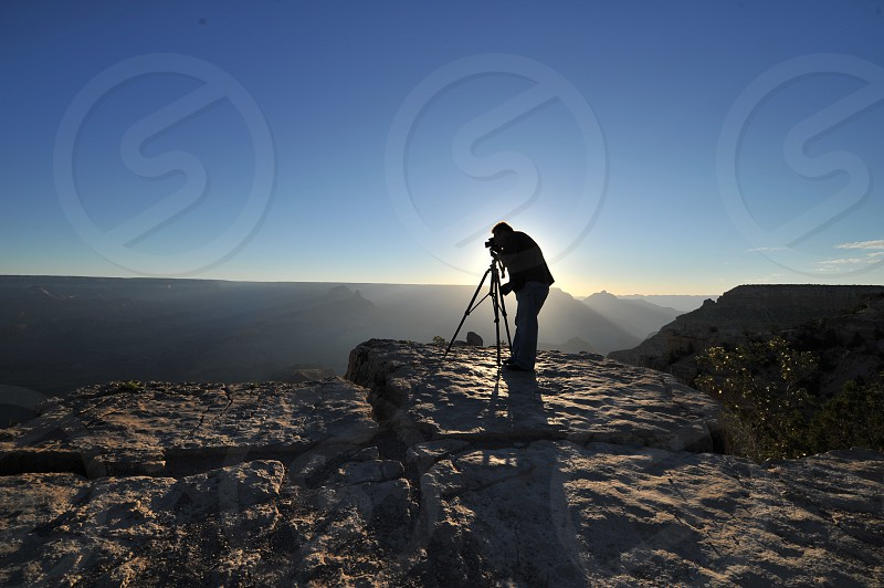 Photographer silhouetted by the sun perched above the Grand Canyon photo