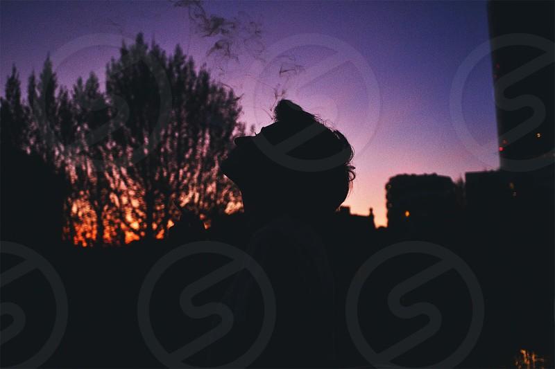 silhouette of man smoking during sunset photo