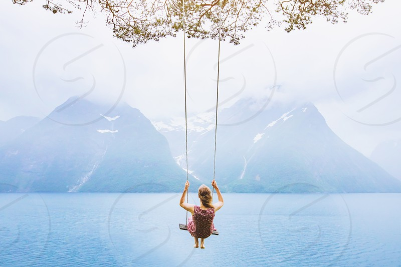 dream concept beautiful young woman on the swing in fjord Norway inspiring landscape photo