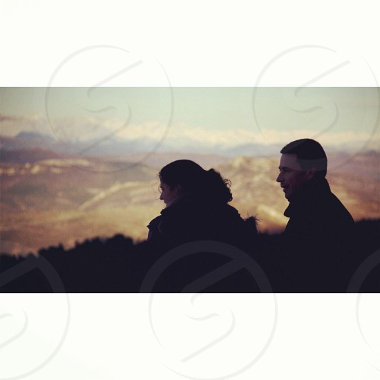 man and woman sitting near mountain photography  photo