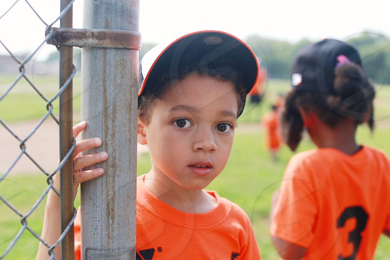 boy in black printed orange crew neck t shirt  and black baseball cap holding brown bamboo post photo