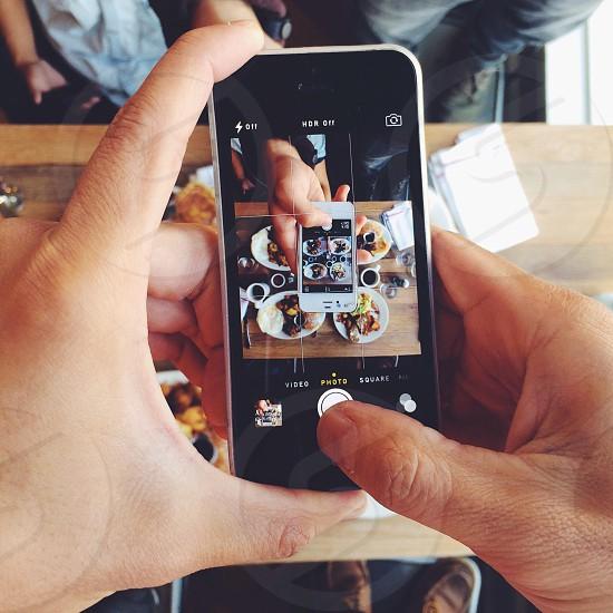 human using black apple iphone photo