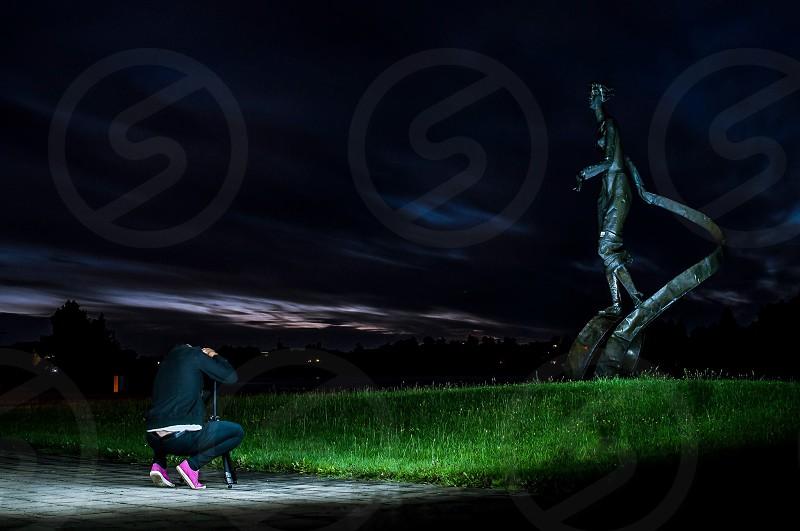 Photographer at work doing long exposure light statue night photography art photo