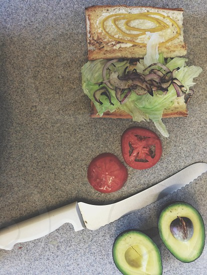 serrated steel knife by sliced tomato and avocado and open sandwich photo