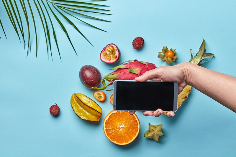 In the women's hand is mobile many different exotic fruits on a blue background decorated with a palm leaf with copy space. Shopping online. Flat lay photo