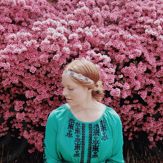 woman in teal and black embroidered blouse standing before pink flowering tree photo