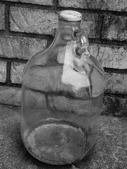 glass jug by a brick wall black and white photo