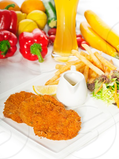 classic breaded Milanese veal cutlets with french fries  vegetables and glass of lager beer on background MORE DELICIOUS FOOD ON PORTFOLIO photo