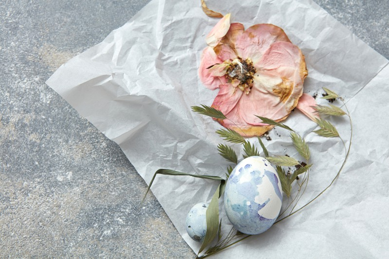 dry flower and chicken eggs on a crumpled paper and a concrete background photo