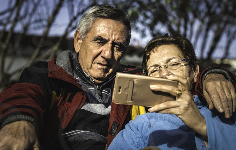 Mature woman with smartphone embraced by her husband while both sitting in park and watching online video photo