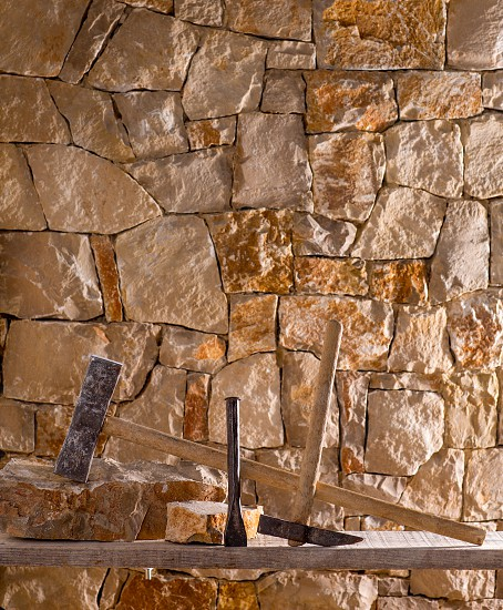 Hammer mason tools of stonecutter masonry work in a contruction stone wall photo