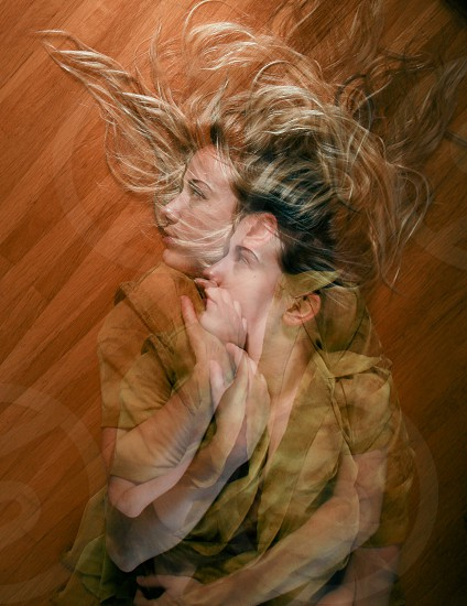 woman's reflection through on brown wooden floor photo