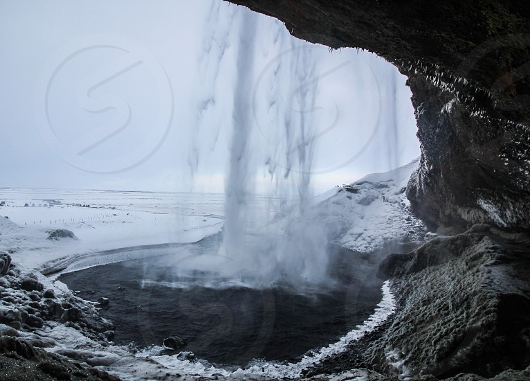 water cascading down cliff with cave photo