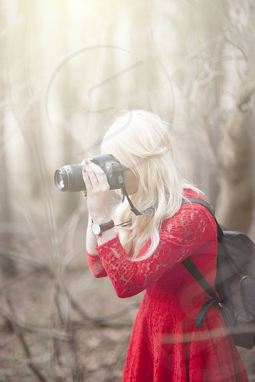 woman in red quarter sleeves dress and black leather backpack taking photo using black dslr camera during daytime photo
