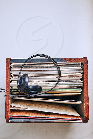 Box with black vinyl records and headphones on the top. Candid people real moments authentic situations photo