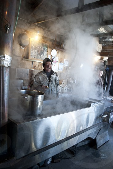 man in grey clothing cooking in kitchen covered in steam photo