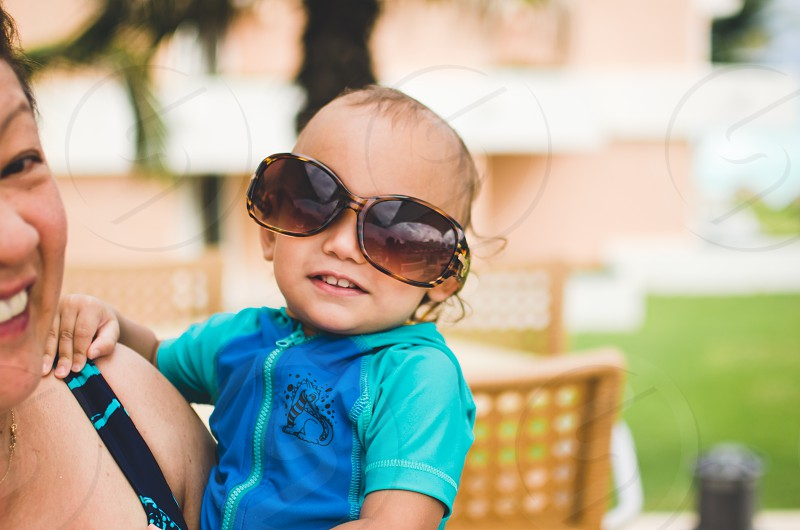 Baby wearing adult sunglasses while being held photo