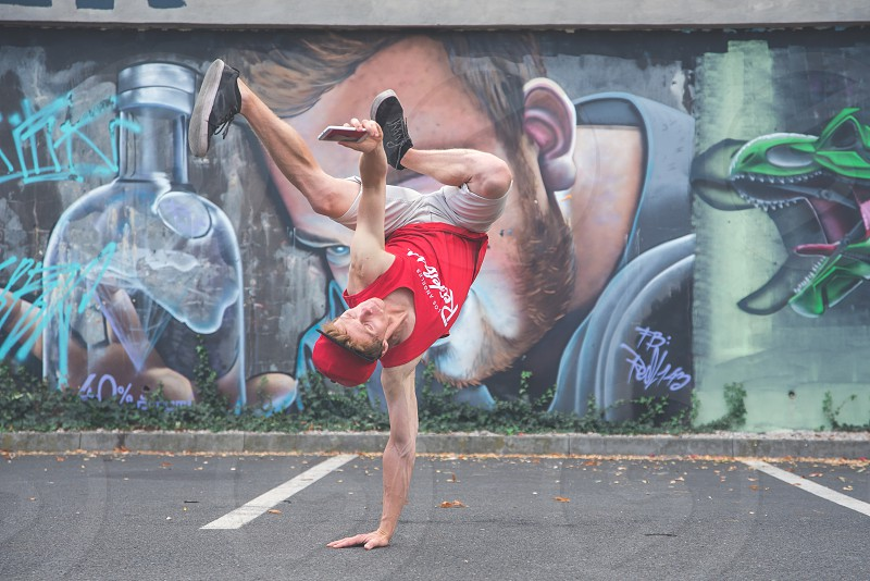 Young man dancing breakdance and photographing on a cell phone on a graphite wall. photo