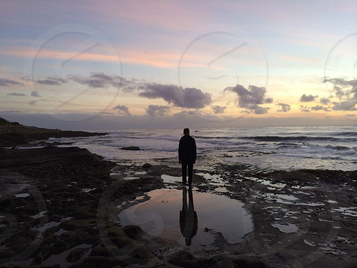 man standing in a shallow pool of water photo