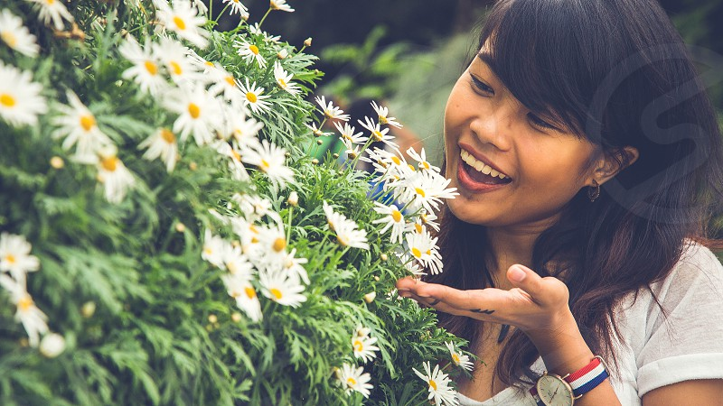 woman in white shirt smiling near white chamomiles at daytime photo